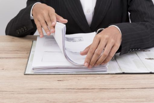 Office worker handles documents on the desk.